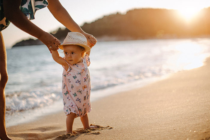 Baby walking holding parents' hands on beach
